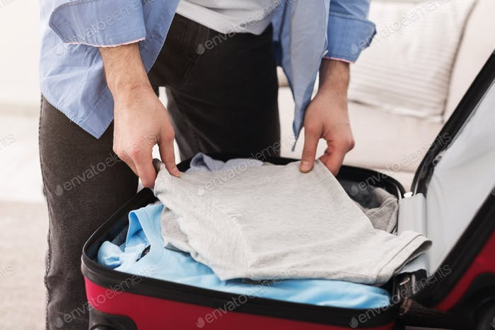 Travel alone. Man packing clothes into suitcase