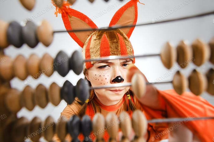 Young woman in the image of red squirrel with abacus