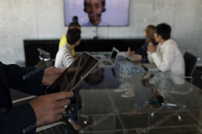 Mid section of Caucasian businessman using digital tablet in modern office