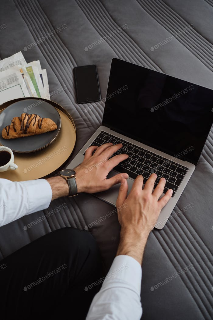 Close up of male hands working on laptop with cellphone, newspapers and croissant with coffee near