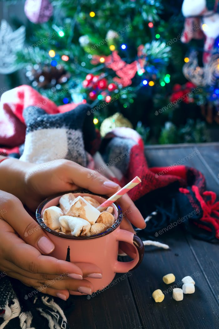 female hand holding cup of hot cocoa or chocolate with marshmallow on wooden table above Christmas