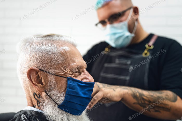 Male hairdresser cutting hair to hipster senior client while wearing face surgical mask