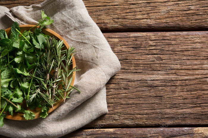Fresh herbs in wooden plate