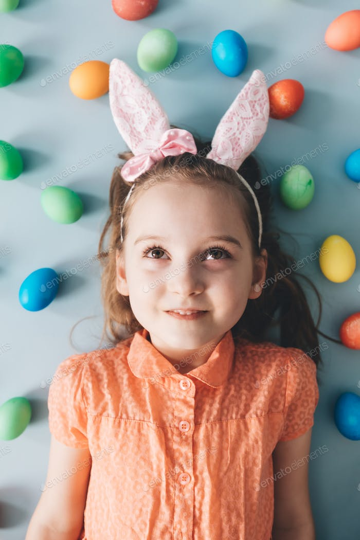 Girl with bunny ears surrounded by colorful eggs.
