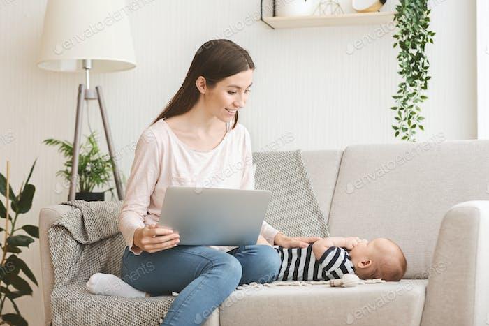 Frau arbeitet am Laptop und kümmert sich um ihr Kind