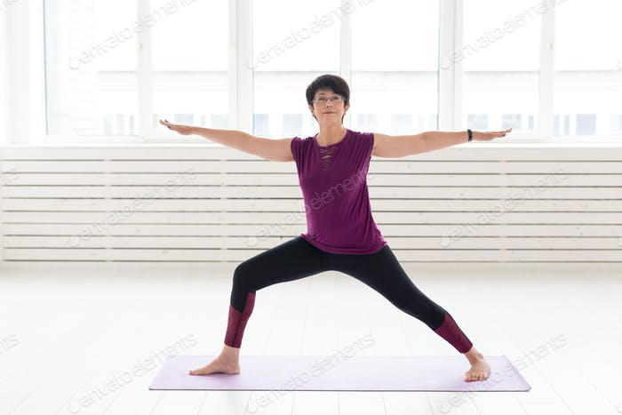 Sport, yoga, people concept - Sporty middle-aged woman practicing yoga indoors