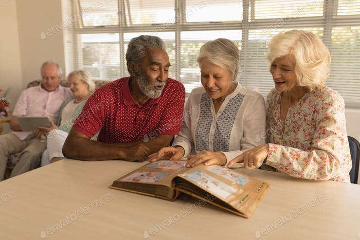 Group of active senior people looking at photo album and showing a photo at nursing home