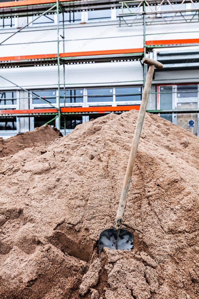 Shovel stuck in the ground at new office and warehouse building construction site