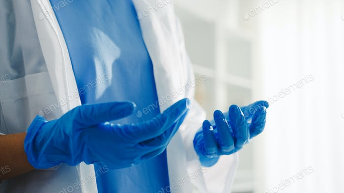 Young lady doctor worker surgeon preparing for the surgical operation and wearing hand gloves.
