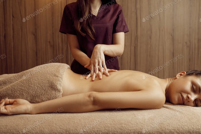 Female masseur pampering back to woman, massage