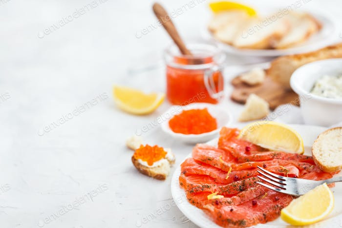 Delicious lunch with salted salmon, red caviar, fresh bread and