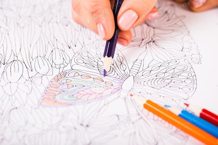 Девушка рисует книжку-раскраска для взрослых с карандашами