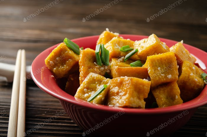Crispy deep stir fried tofu cubes with chives in clay dish on wooden kitchen table