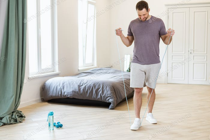 Man Exercising With Jumping Rope At Home, Wearing Casual Clothes