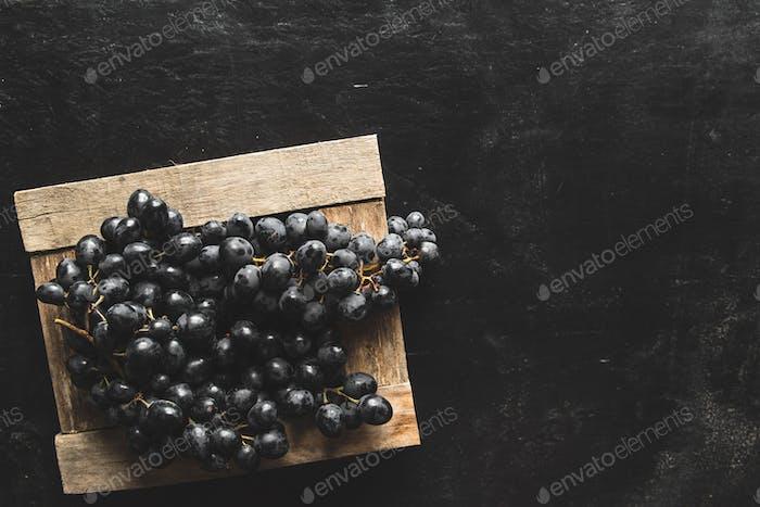 auf einem grauen Hintergrund eine dunkle Traube in einer Holzkiste