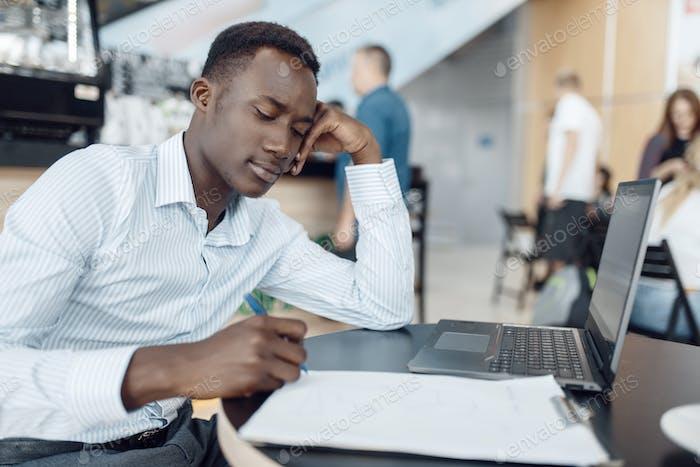 Ebony businessman working on laptop in office