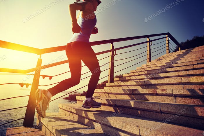 Healthy lifestyle woman running upstairs on sunrise seaside