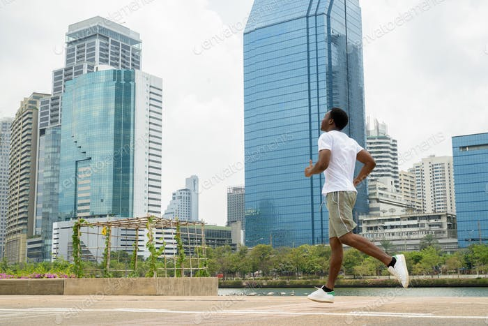 Young African man running outdoors in park with cityscape