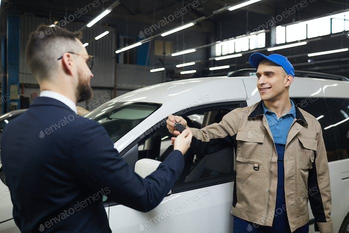 Mann gibt Schlüssel für Auto Service Worker