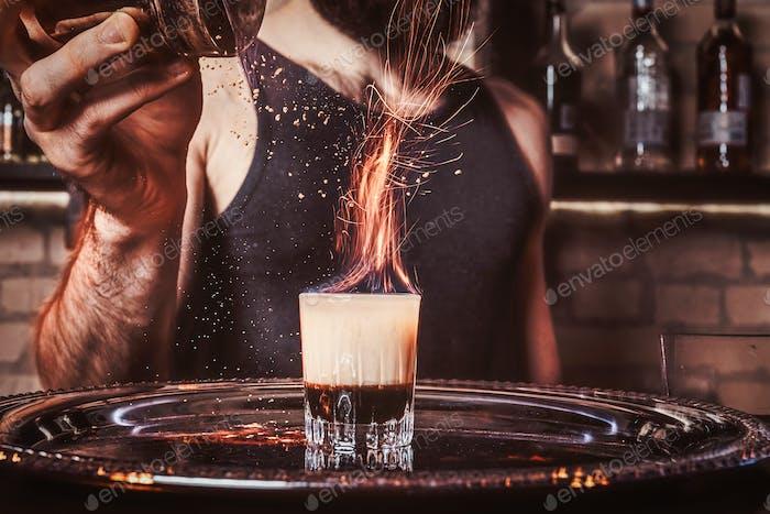 Ein bärtiger Barkeeper gießt einen Zimt in einen Cocktail