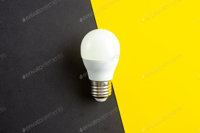 Top view of standard incandescent light bulb on black yellow mixed colors background with free space