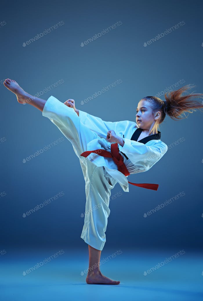 Young girl training karate on blue background