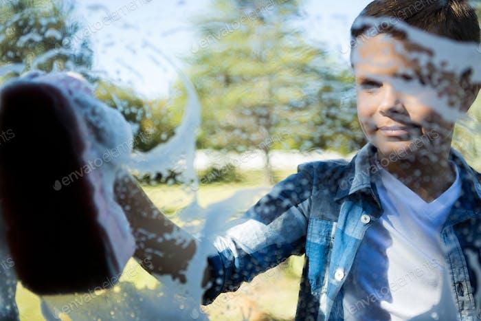Teenage boy washing a car