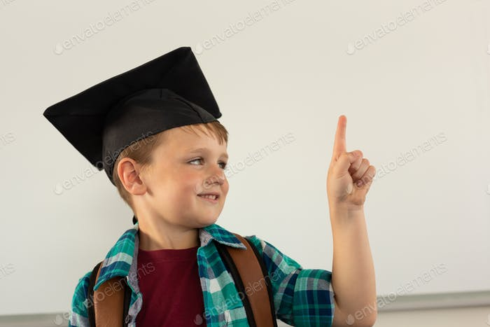 Happy Caucasian boy in graduation cap pointing his finger in a classroom at elementary school