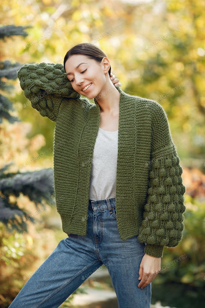 Girl in a kniten sweater standing on trees background