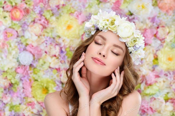 sinnliche junge Frau im Blumenkranz mit perfekter Haut