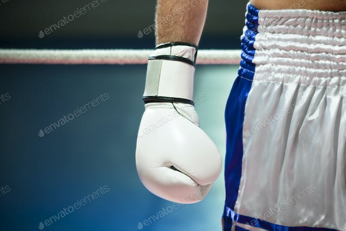 Closeup Of Boxing Gloves With Boxer Athlete On Ring
