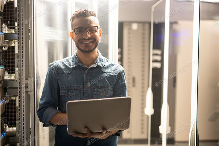 Cheerful server engineer in datacenter room