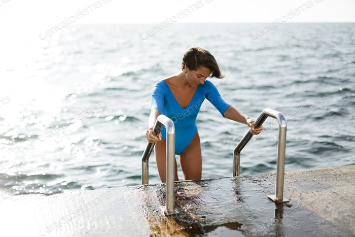Pretty woman with dark short hair in blue swimsuit going down by the stairs in sea