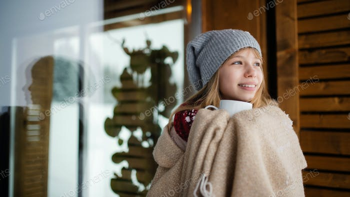 Preteen girl wrapped in blanket with hoit drink in front of wooden cottage in winter nature.