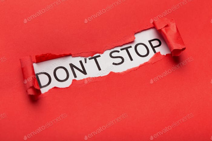 Dont stop phrase bursting out from torn red paper