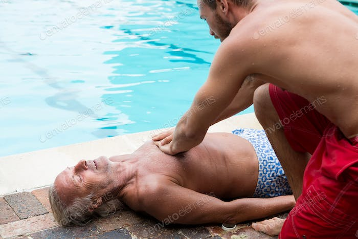 Lifeguard pressing chest of unconscious senior man