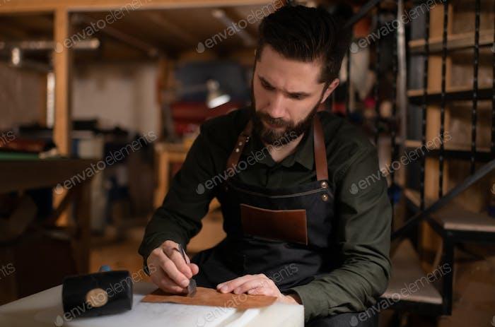 Fokussierter Handwerker kreieren Ornament auf Lederstück