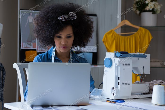 Female fashion designer working on laptop