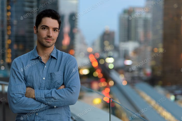 Portrait of young handsome man outdoors at night in city
