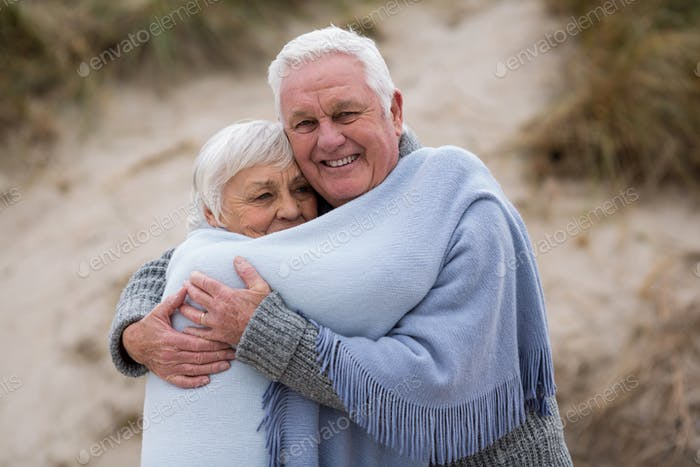 Senior couple wrapped in shawl on the beach