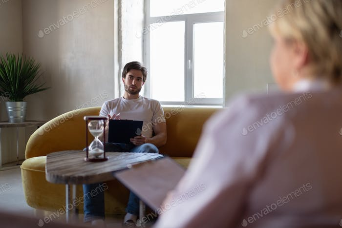 Male patient speaking to psychologist and drawing on clipboard