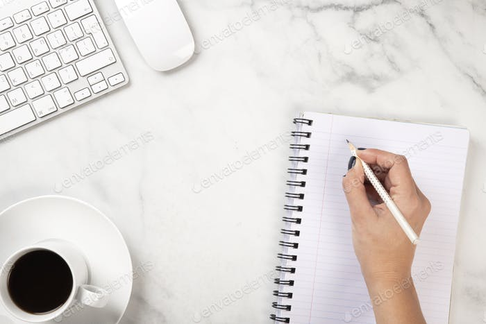 A hand writing on a notebook on a marble texture desk with coffee, keyboard and a mouse