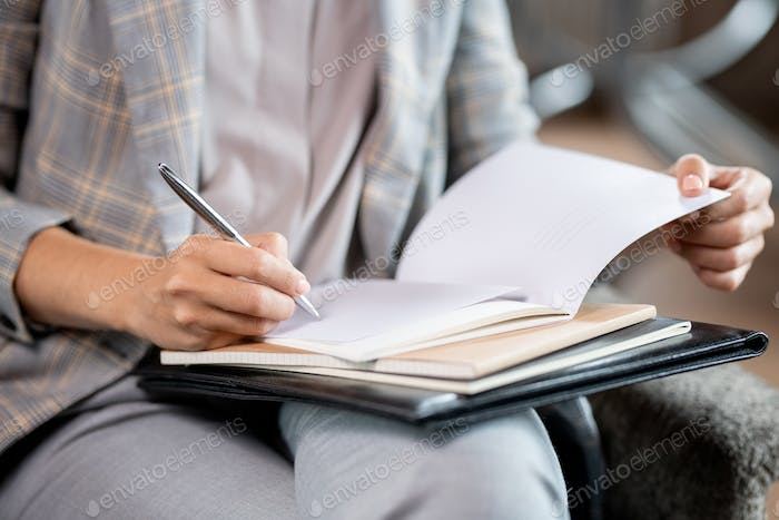 Young school teacher with pen correcting mistakes or putting mark in copybook