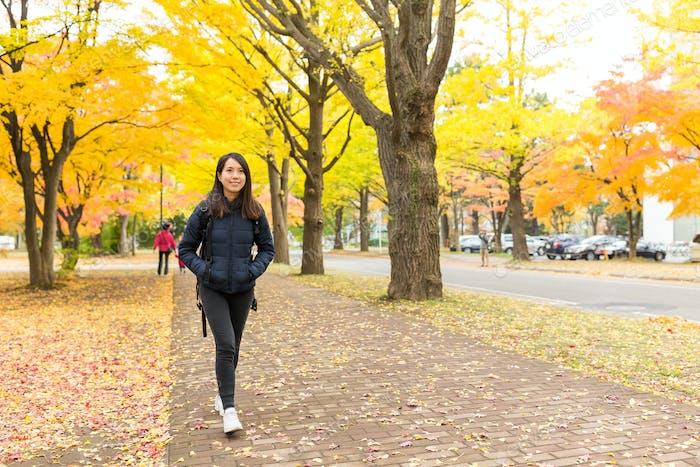 Woman walking at outdoor with gingko tree plant