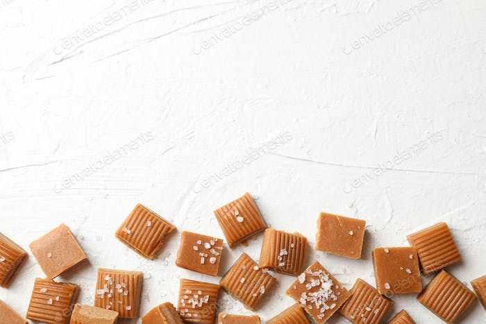 Salted caramel candies on white cement background, space for text