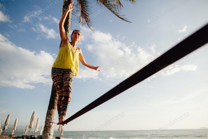 teenage girl  balancing on slackline with sky view