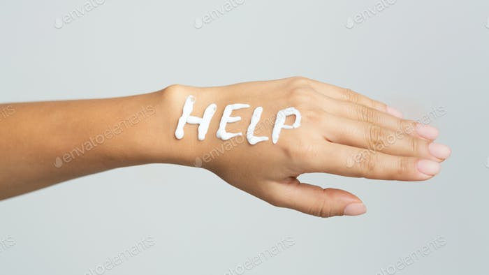 Word help written with cream on female hand