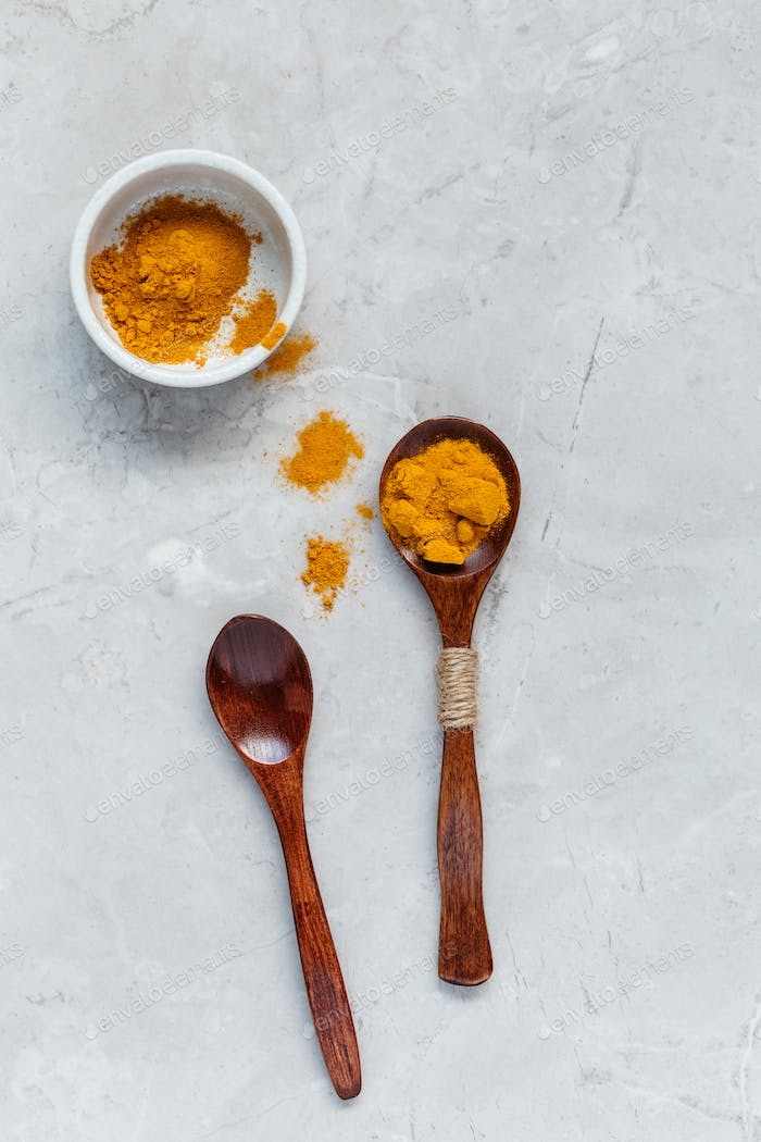 Top view of Ground Turmeric with Wooden Spoons