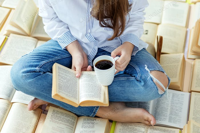 A young woman reads a book and drinks coffee. Concept for World Book Day, lifestyle
