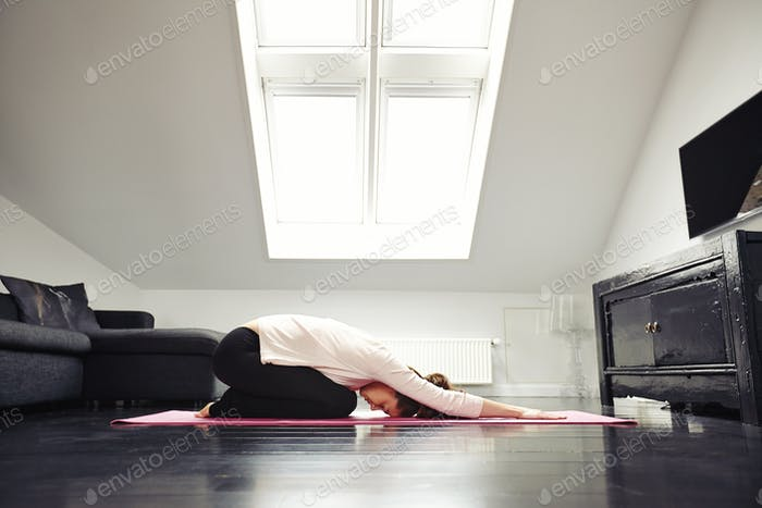 Junge kaukasische Frau Ausübung Yoga im Wohnzimmer